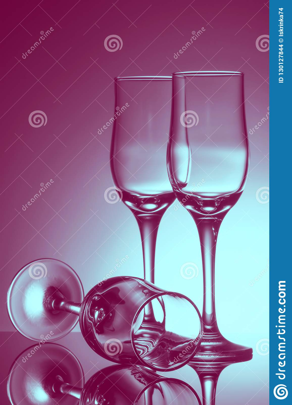 Three empty champagne glasses on colored background