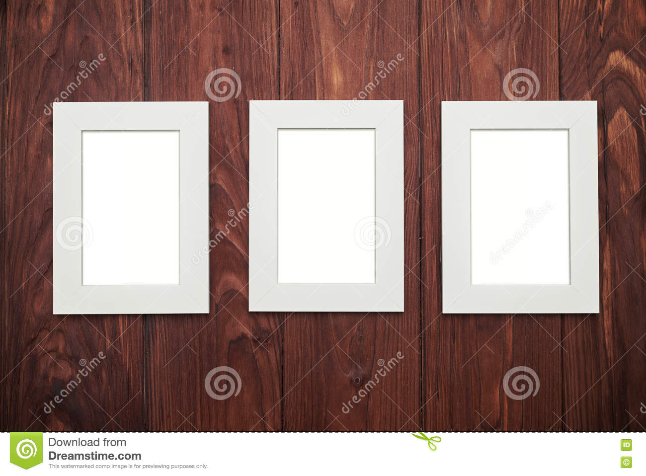 Three empty frames in the middle on brown wooden desk