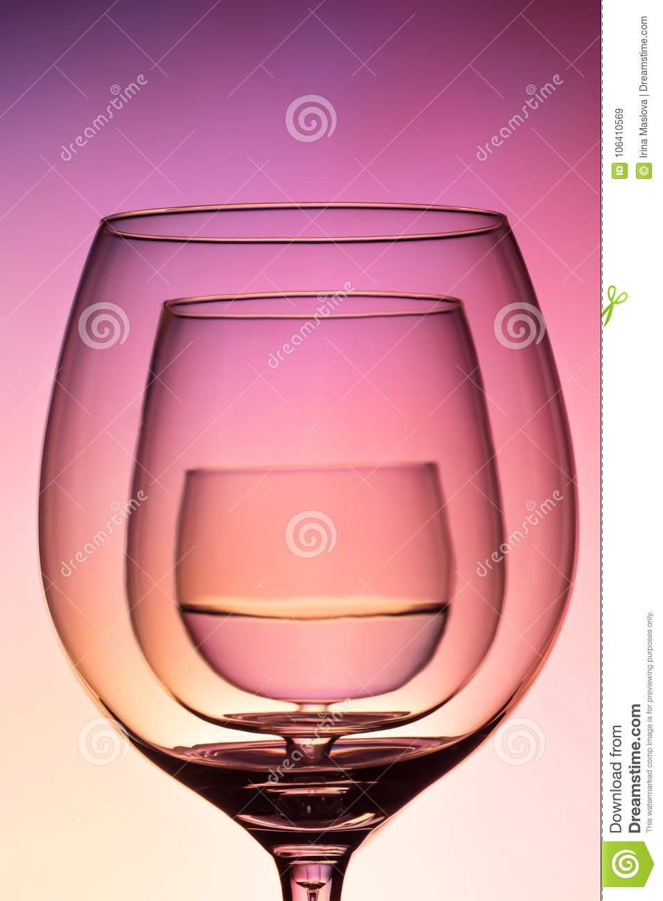 Three empty wineglass for red wine on diffusion lit background in abstract composition with reflection