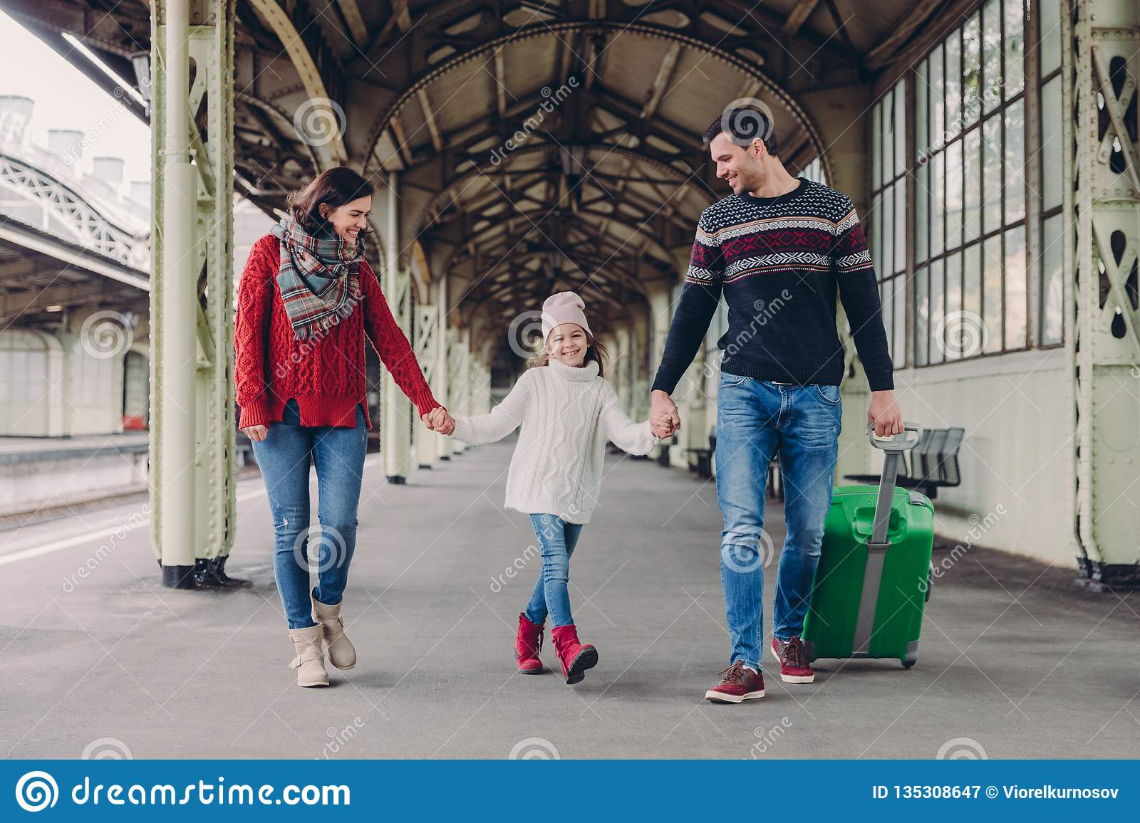 Three family members on railway station. Happy mother, daughter and father have positive facial expressions, waits for train on