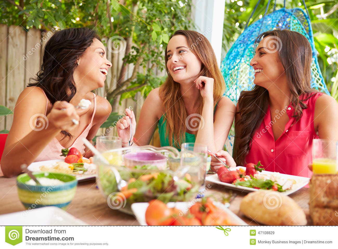 Three female friends enjoying meal outdoors at home stock for Meal outdoors