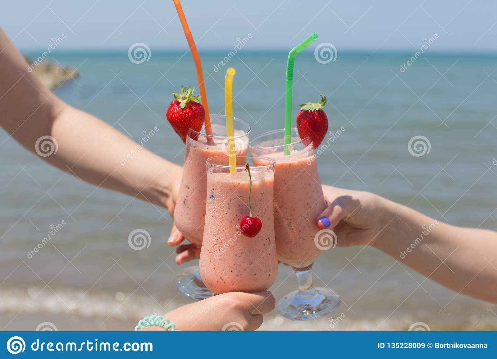 Three female hands are holding strawberry milkshakes on the background of the sea