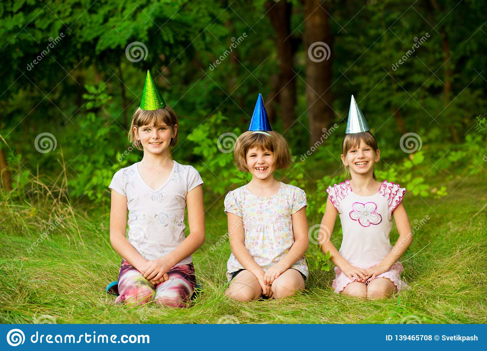 Three friendly children in festive cone caps, sit on grass, have fun together as celebrate birthday