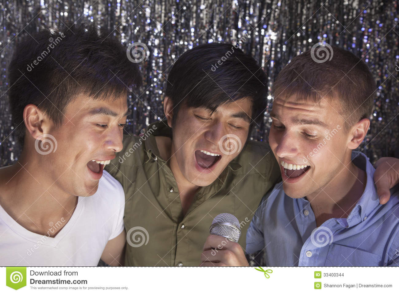 Three friends with arm around each other holding a microphone and singing together at karaoke