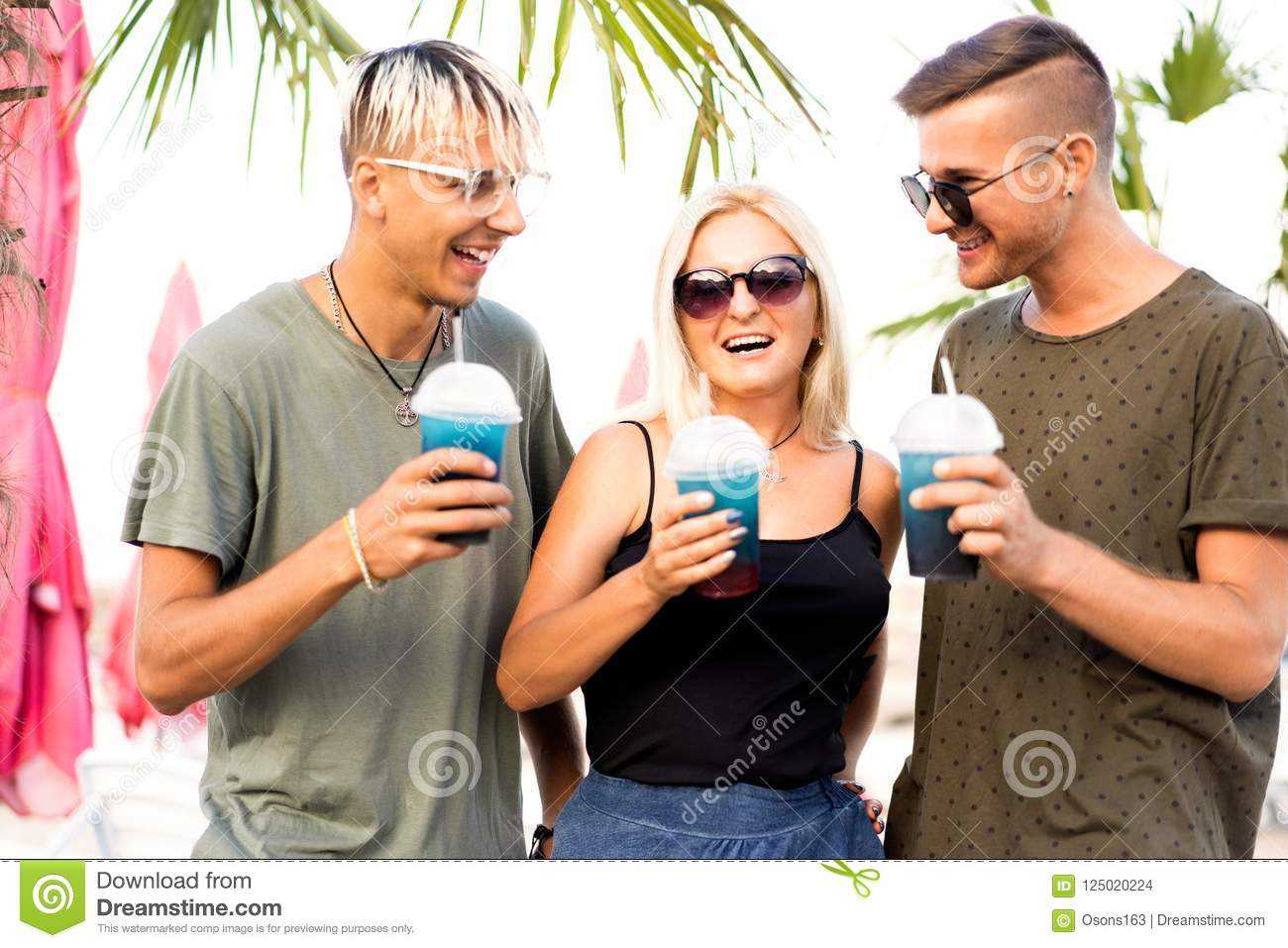 three friends cheerful company rest on a tropical beach and drink cocktails, very, magazine concept