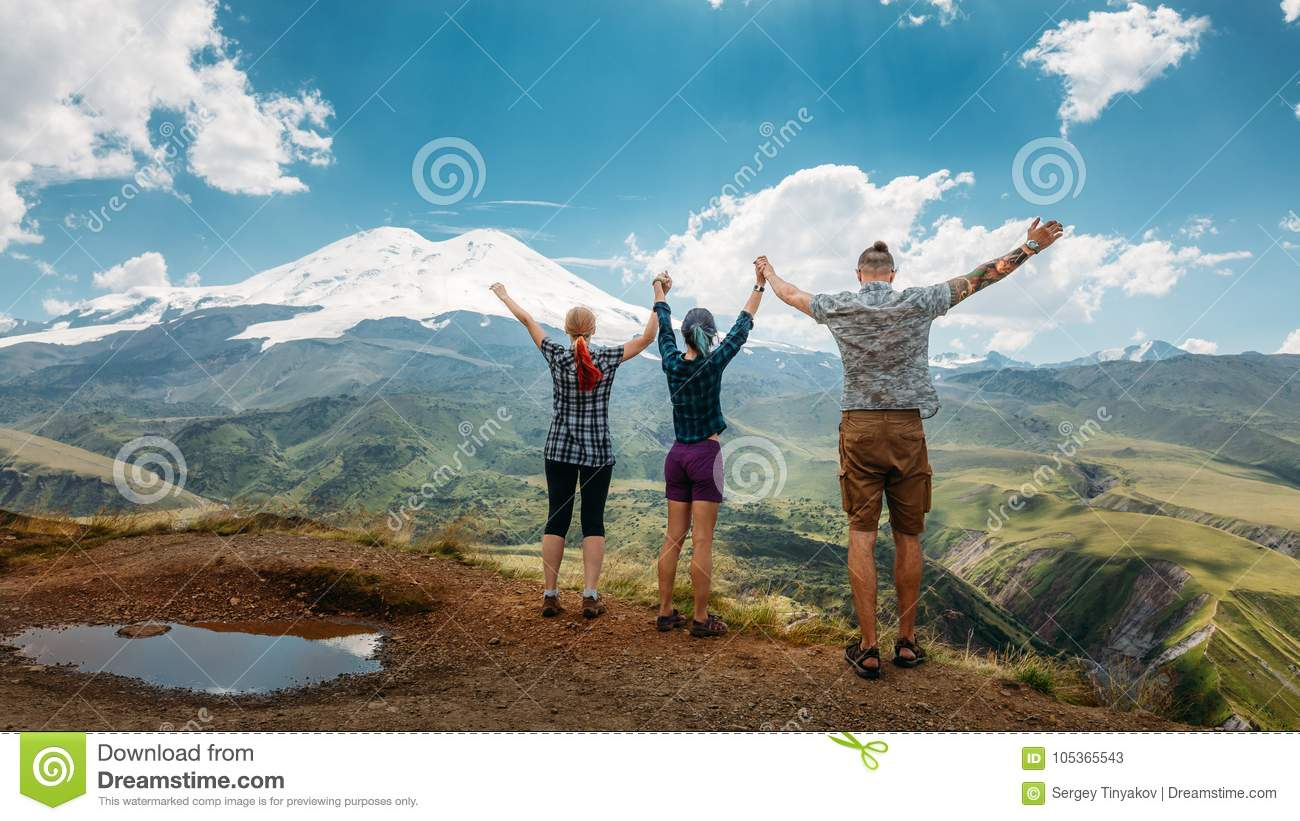 Three friends joined hands and raised their hands up, enjoying the view of the mountains in the summer. Summer Vacations Outdoor C