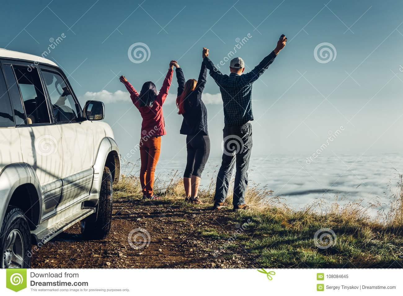 Three friends joined hands and raised their hands up, enjoying the view of Outdoor.Vacations Journey Concept