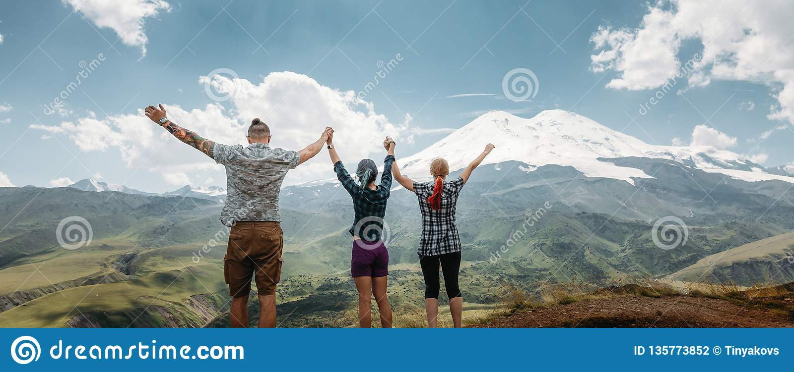 Three friends joined hands and raised their hands up, enjoying the view of the mountains in the summer. Lifestyle Travel Happy
