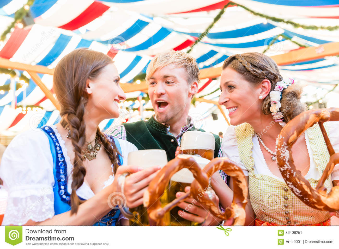 Friends eating giant pretzels and drinking in beer tent