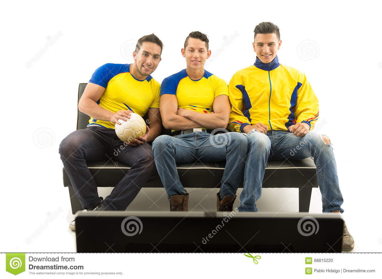 Three friends sitting on sofa wearing yellow sports shirts watching television with enthusiasm, white background, shot