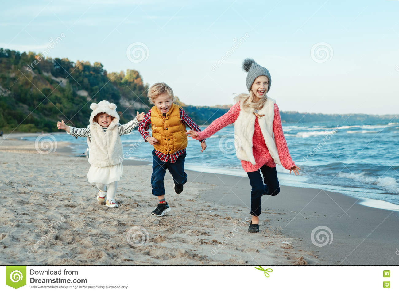 Three funny smiling laughing white Caucasian children kids friends playing running on ocean sea beach on sunset outdoors
