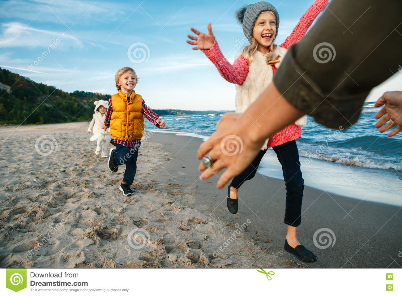 Three funny smiling laughing white Caucasian children kids friends playing running to mother parent adult on ocean sea beach