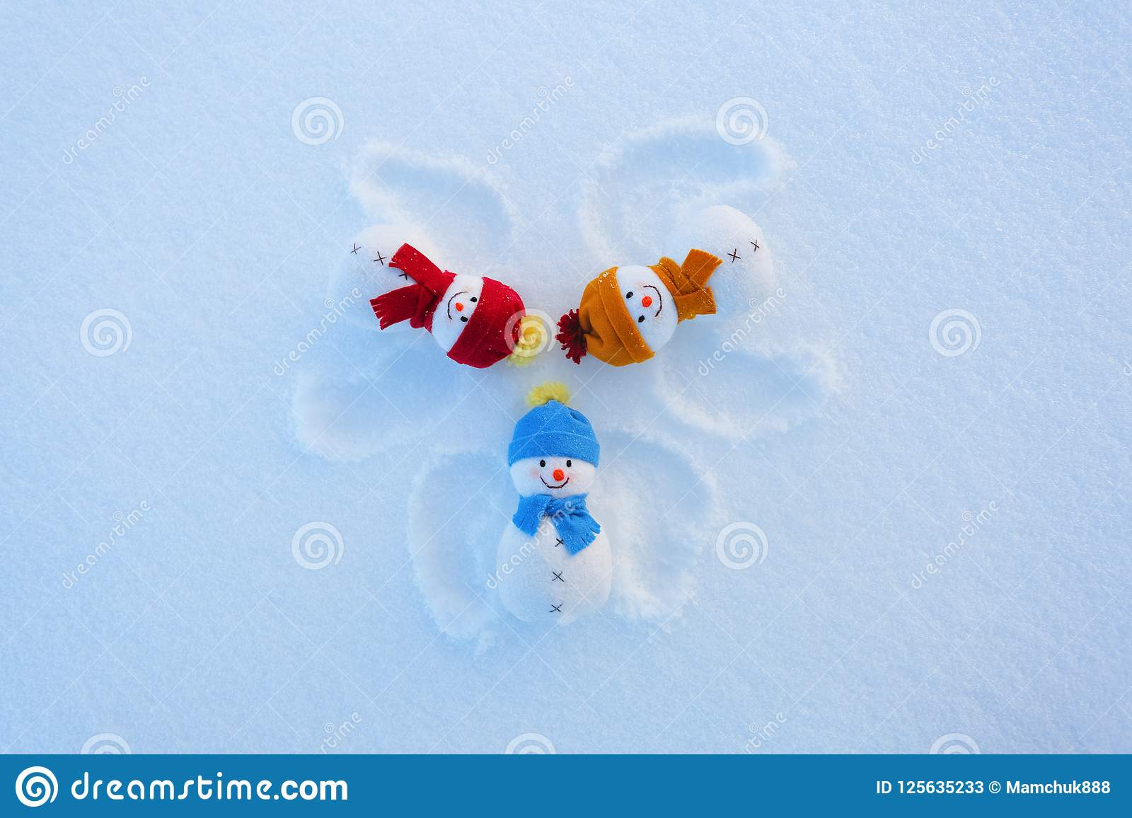Three funny snowman in hats and scarfs are laying on the snow with drawn wings. Fractured outprints. Happy new year.