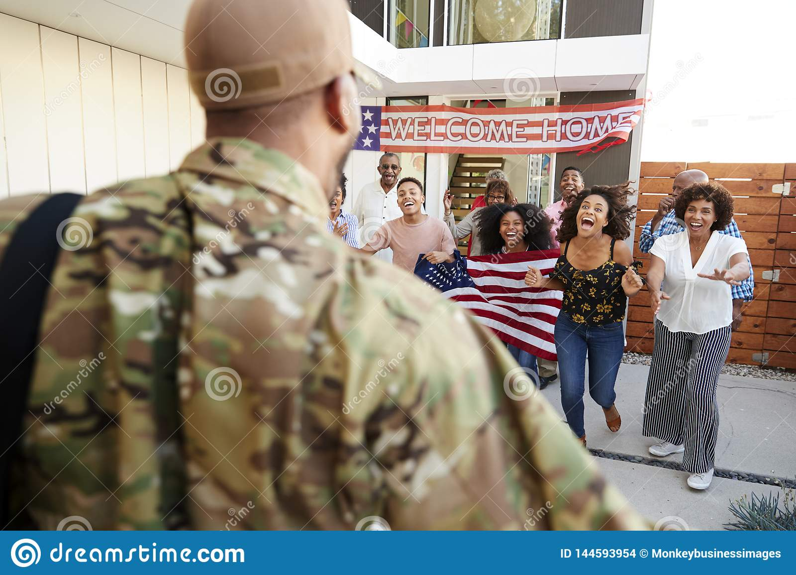 Three generation African American  family welcoming soldier returning home,over shoulder view