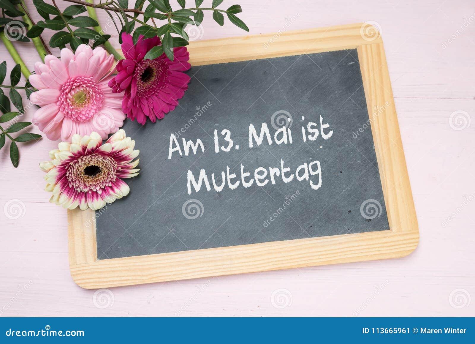 Three Gerbera Flowers On A Writing Chalkboard German Text Am 13