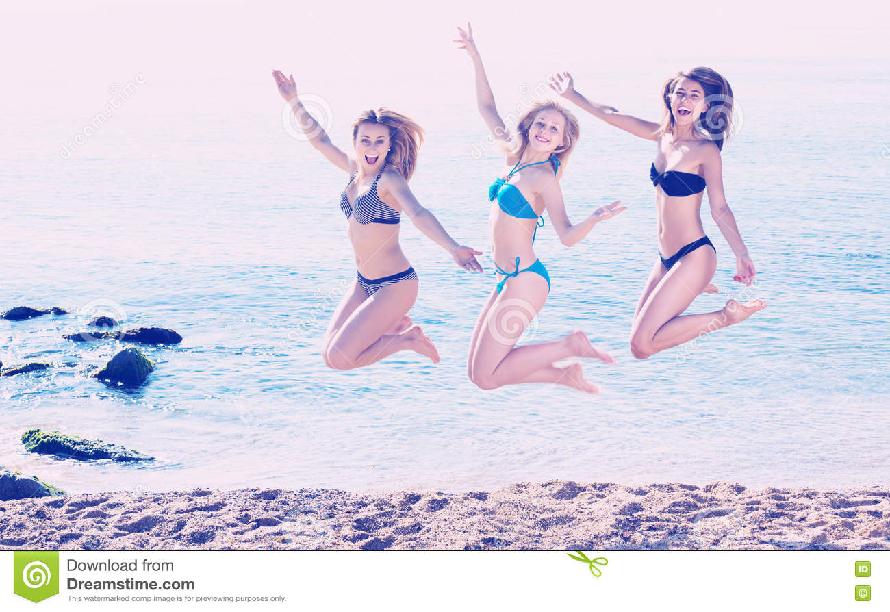 e8ce1ad476e6c Three Girls Jumping On Beach Stock Photo - Image of happy, laughing ...