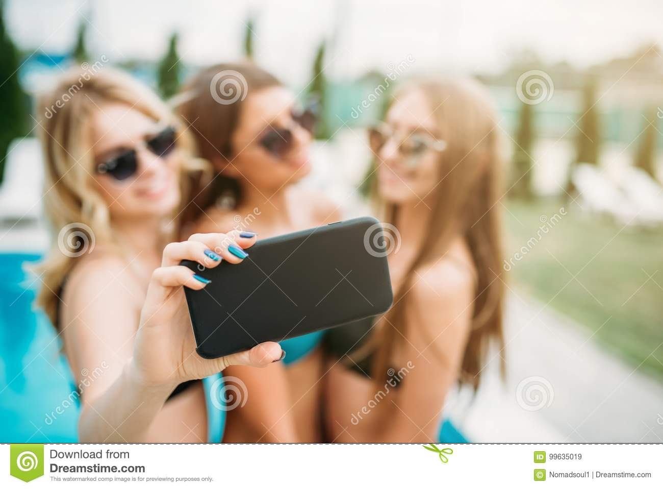 6fd22da4e5 Three girls in swimsuits and sunglasses makes selfie near the swimming pool.  Resort holidays. Tanned women on summer holidays