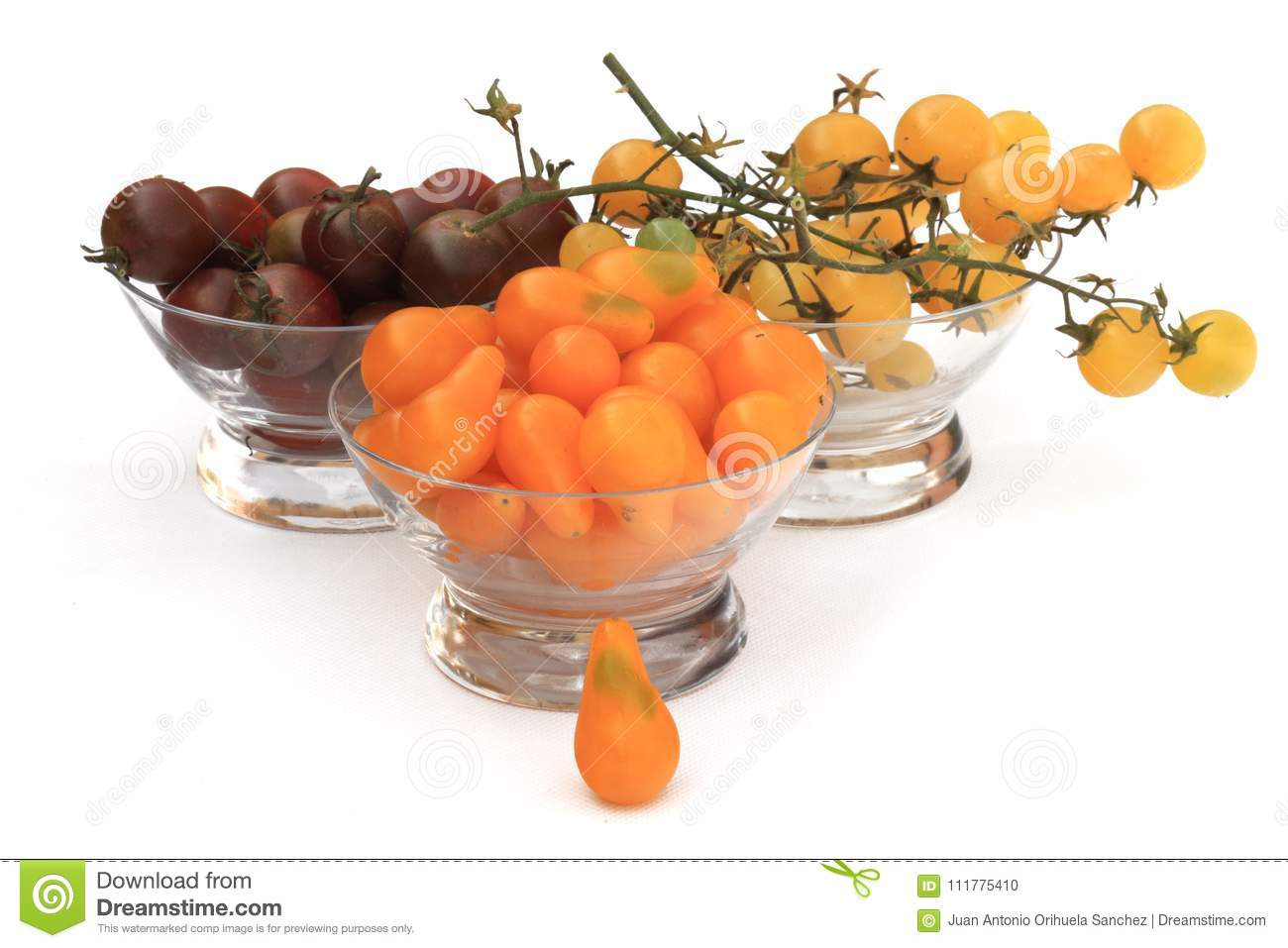 Three glass bowls filled with cherry tomatoes three different types