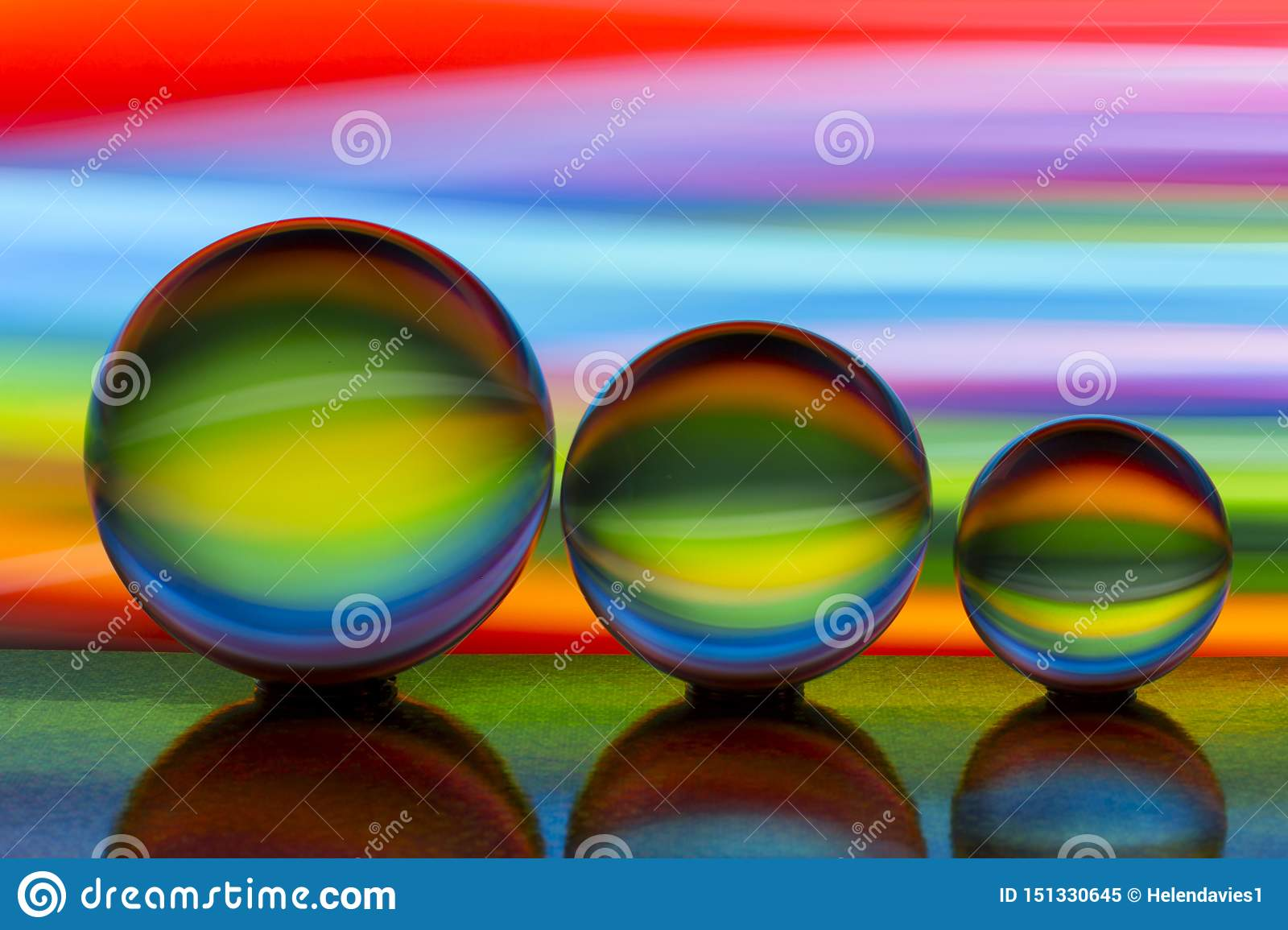 Three glass crystal balls in a row with a rainbow of colorful light painting behind them