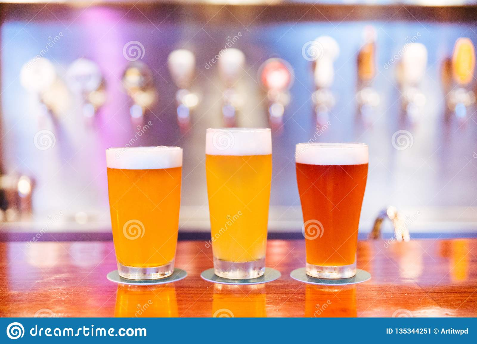 Three glasses of craft beer with foam and different colors from light to dark on wooden counter with blur and bokeh.