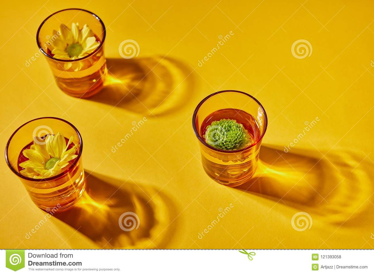 Three glasses of water and flowers on a yellow paper background with shadow
