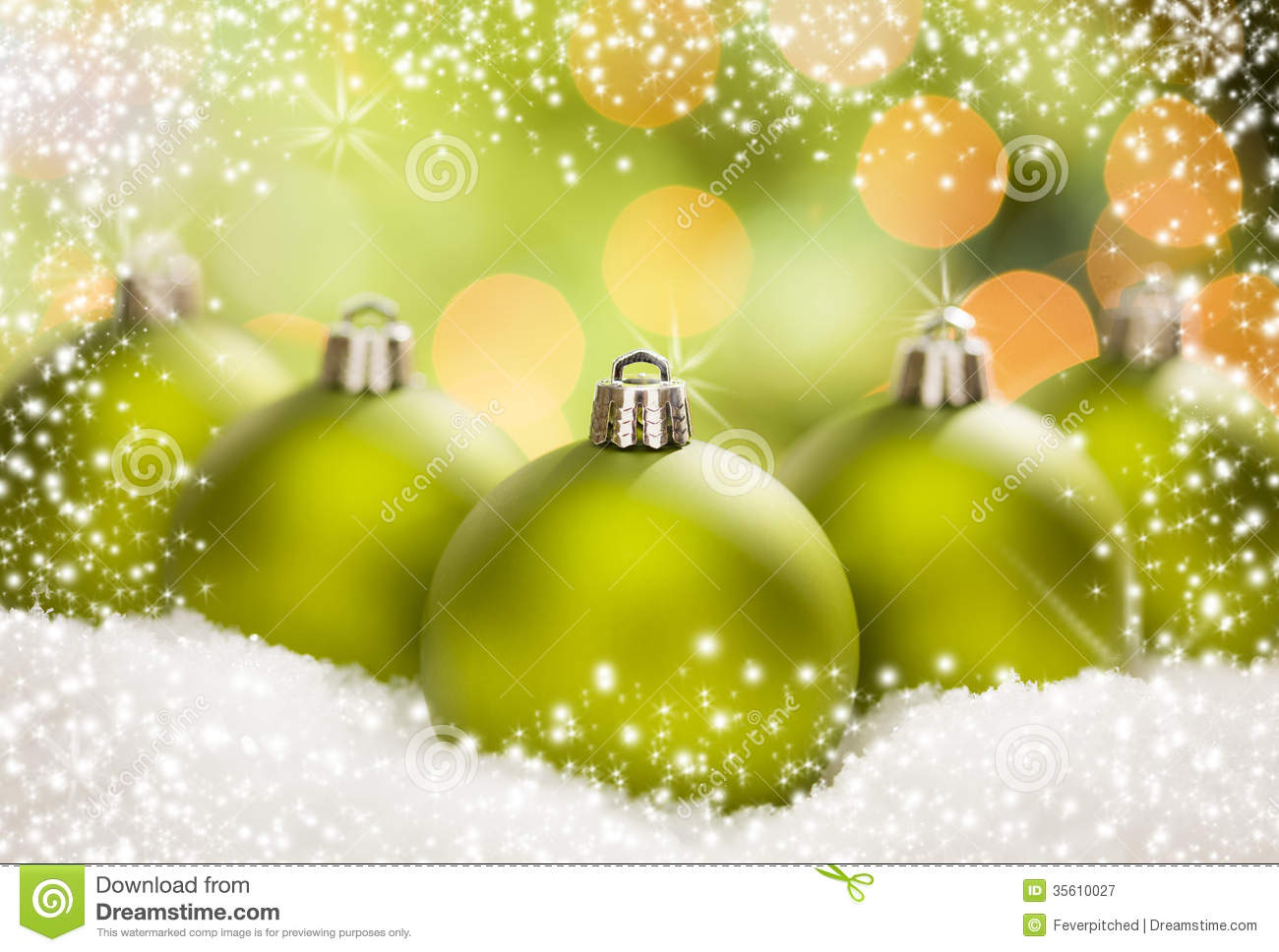 Three Green Christmas Ornaments On Snow Over An Abstract Background