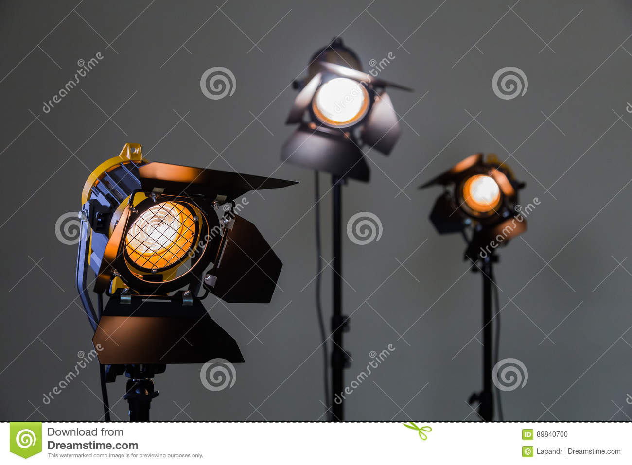 Three halogen spotlights with Fresnel lenses on a grey background. Photographing and filming in the interior