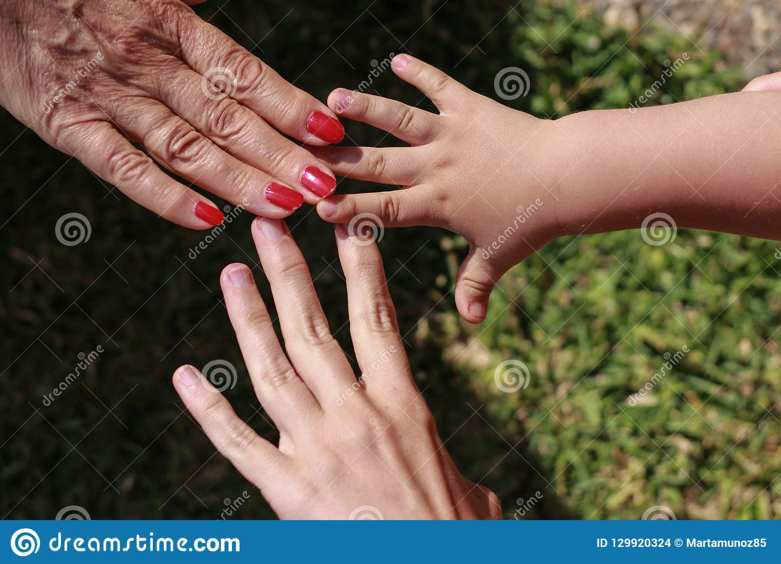 Three hands of family: son, mother and grandmother.