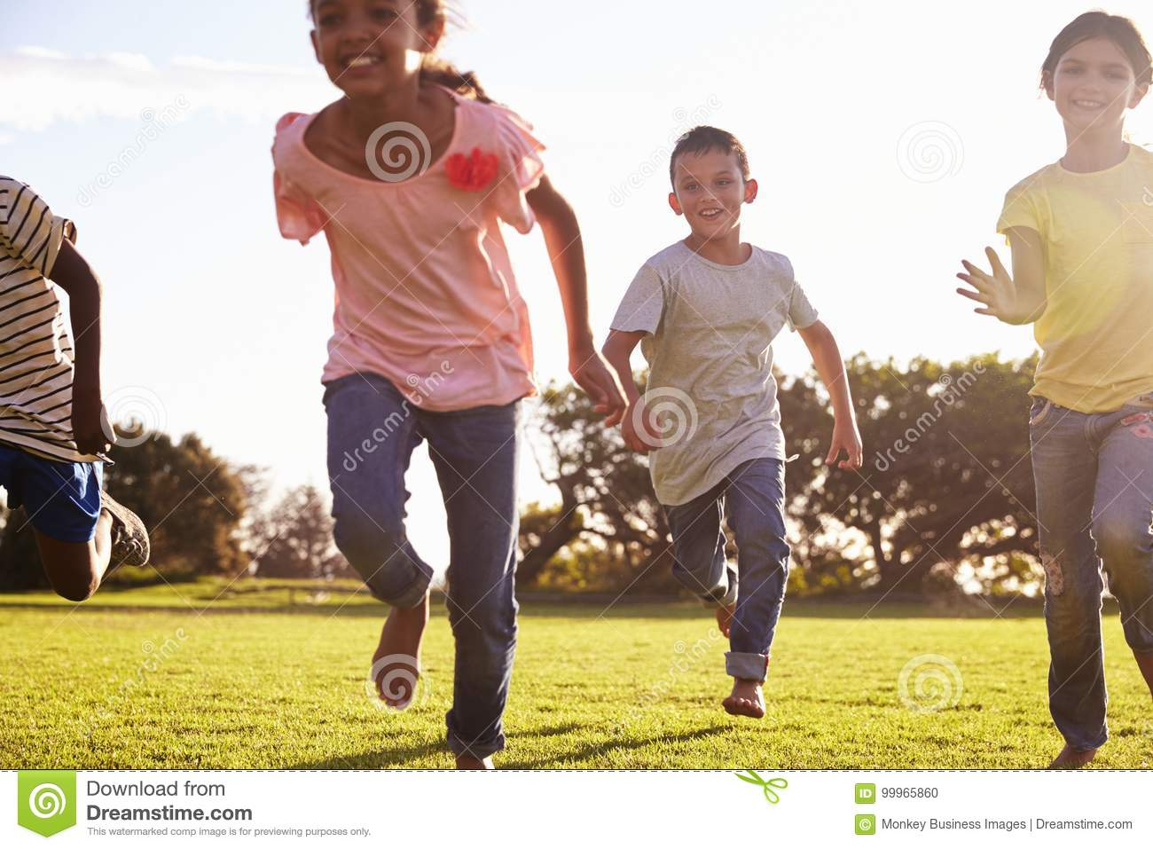 Three happy children running barefoot in a field in Summer