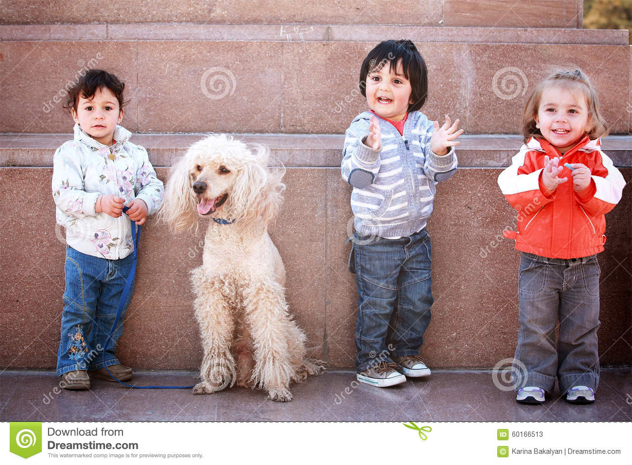 Three happy young children with pet dog.
