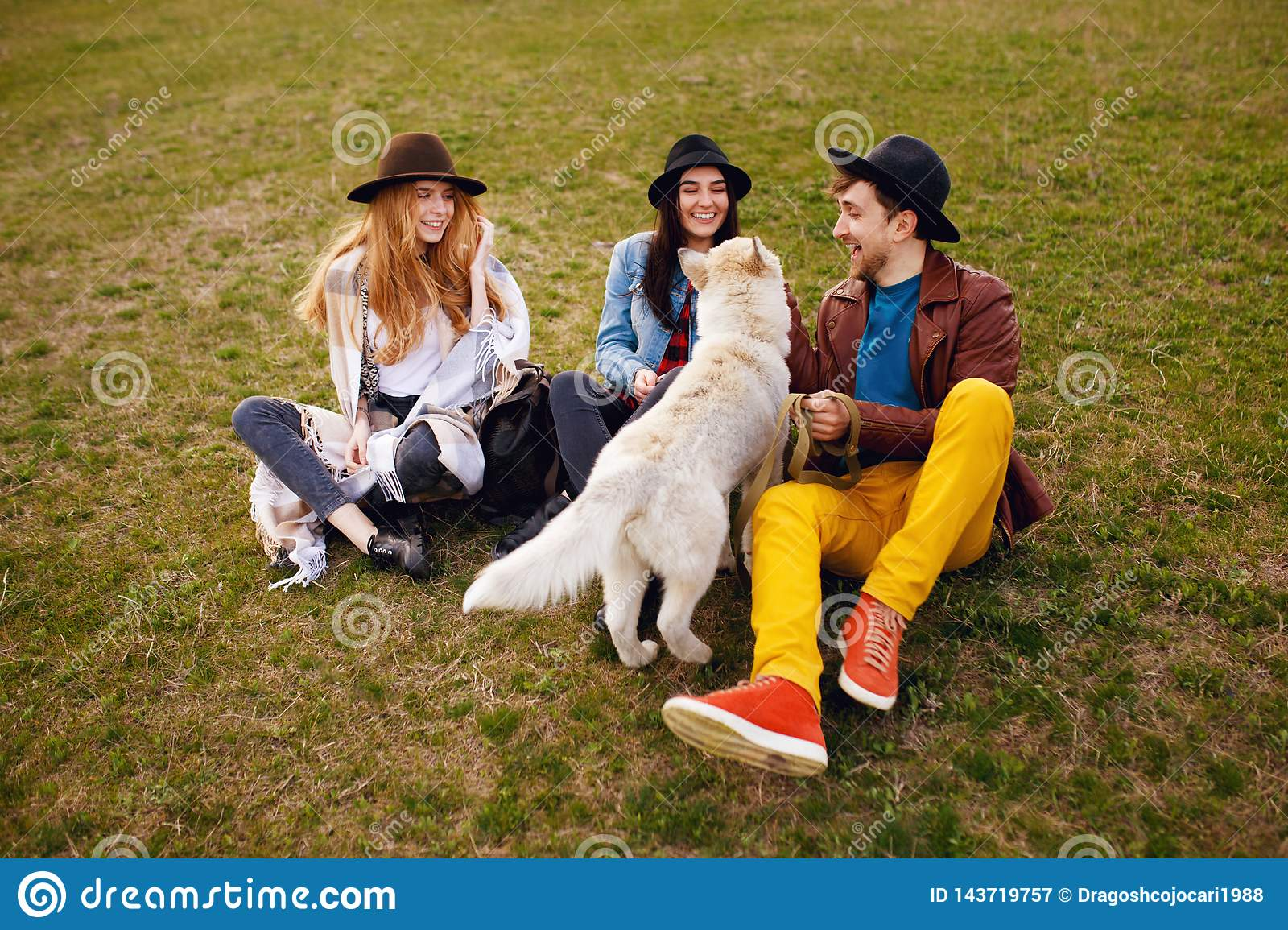 A three happy young stylish friends spend time outdoors together with their husky dog sitting on green grass.