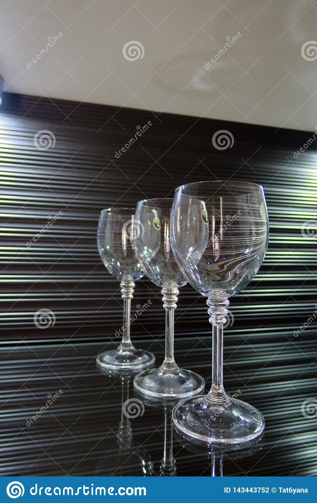 Three high transparent glasses on a beautiful brown background