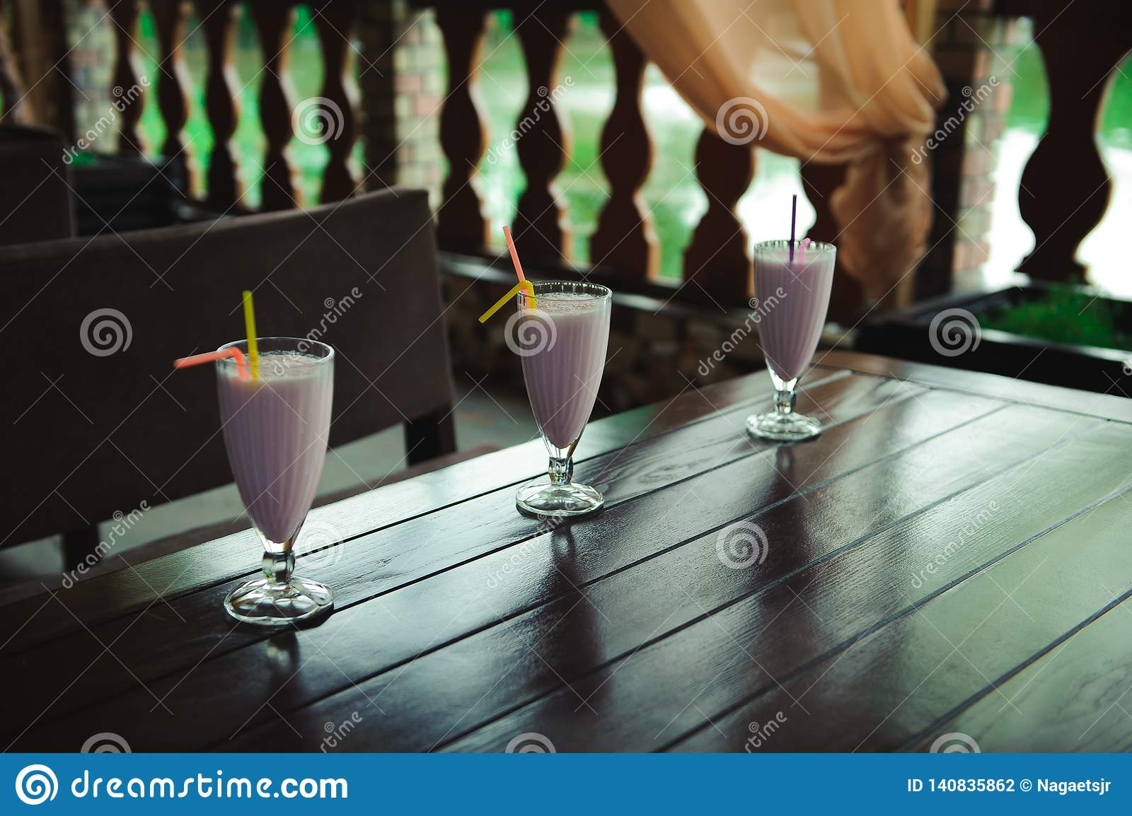 Three jars of pink berry milkshakes with straws on old wooden table.