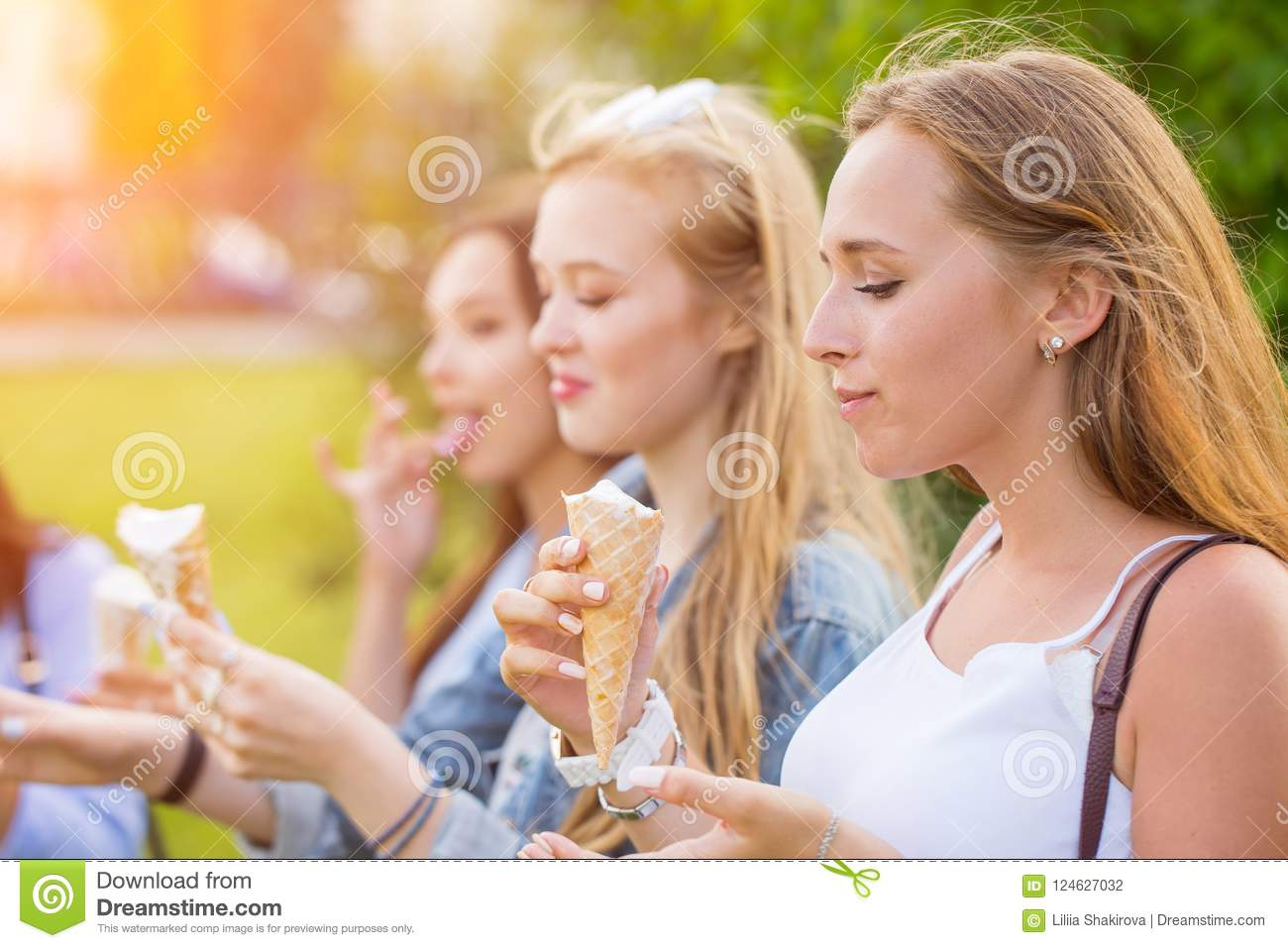 Three joyful young girlfriends on a promenade standing in a row smiling happily eat ice cream cones on summer vacation