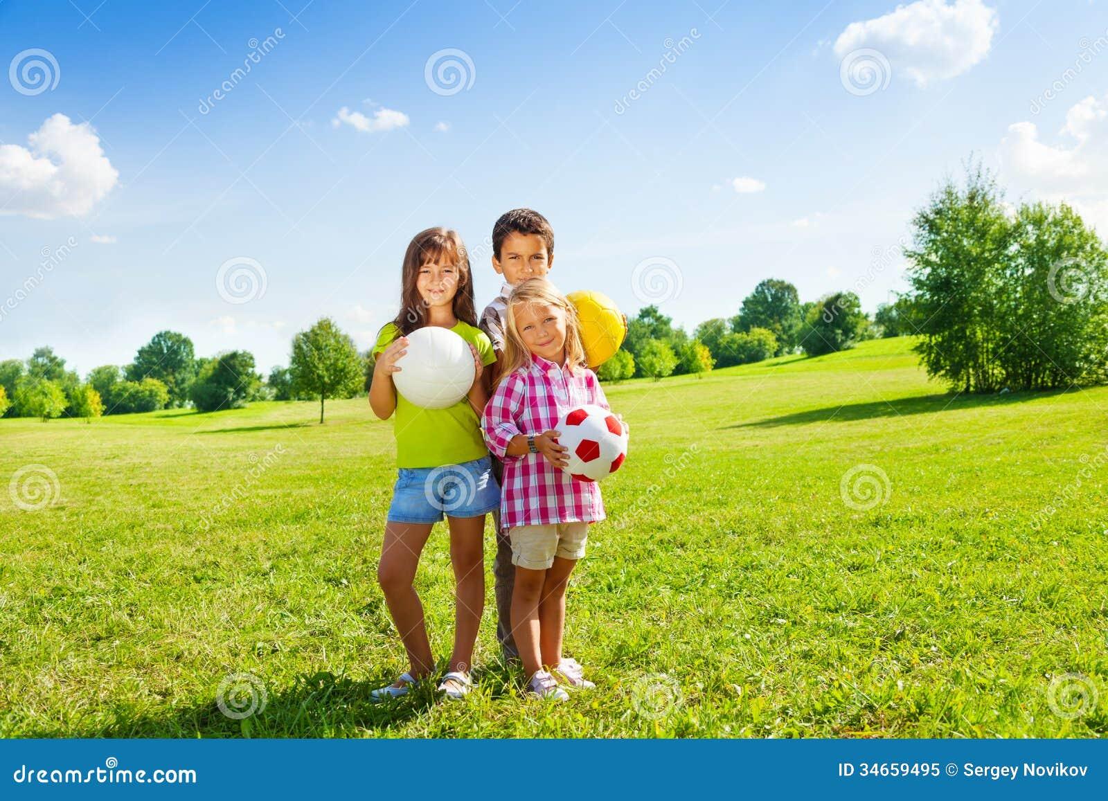 Three kids with sport balls