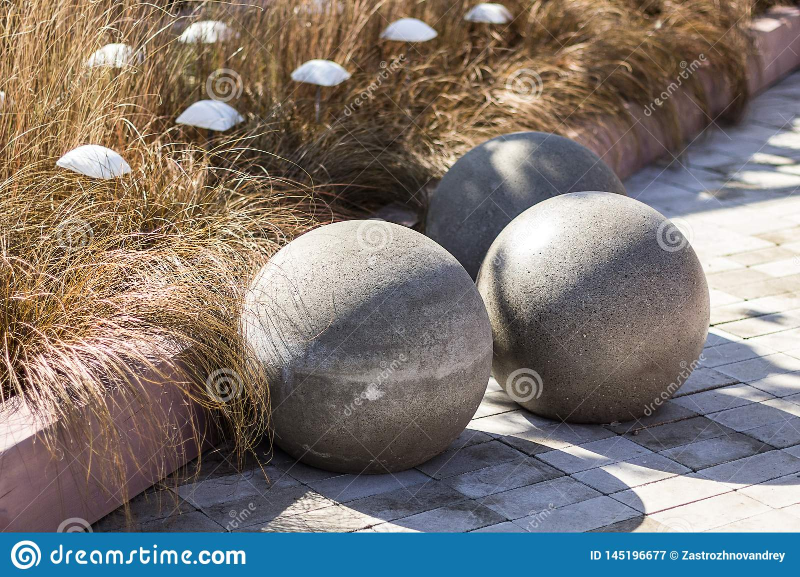 Three Large Concrete Spheres On The Background Of Yellow Grass