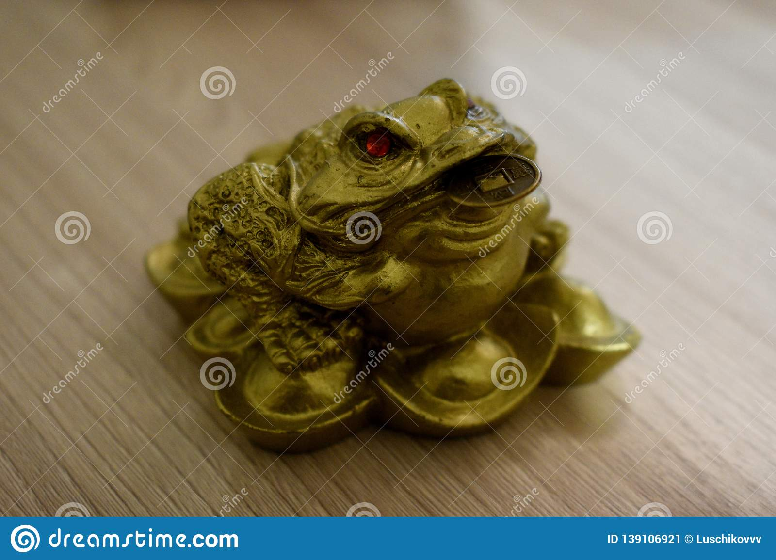 Three-legged money toad with a coin in his mouth.