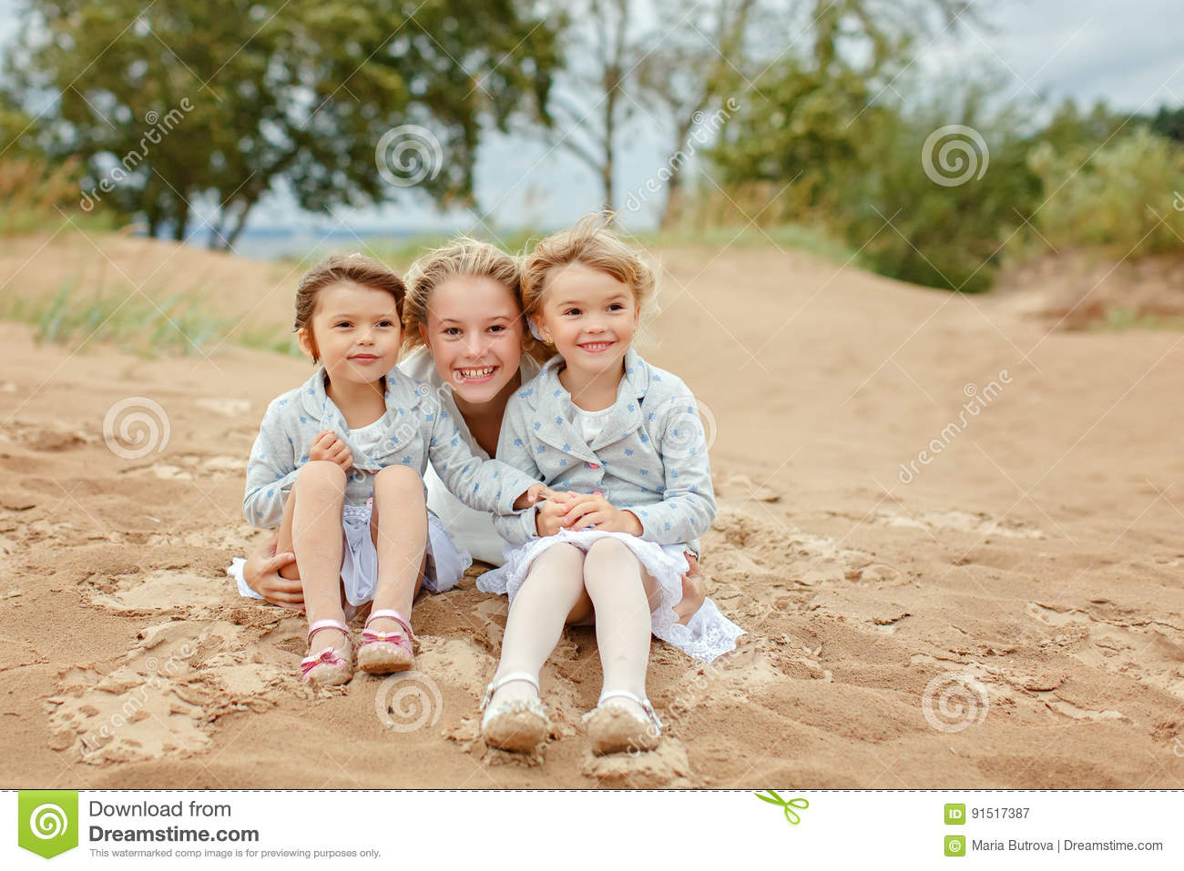 Three little girls are adorable sisters hugging on the background of the sea in windy summer weather