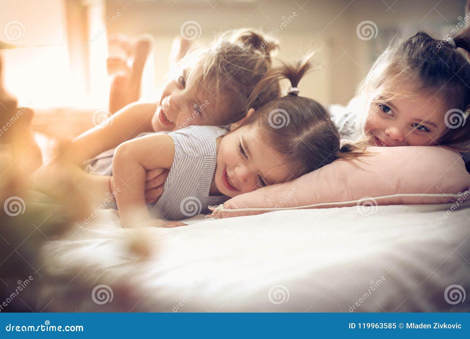 Three little girls in bed.