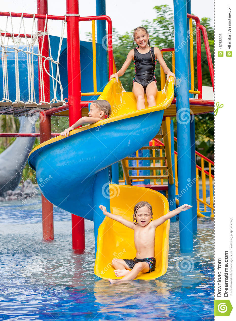 Three Little Kids Playing In The Swimming Pool Stock Photo