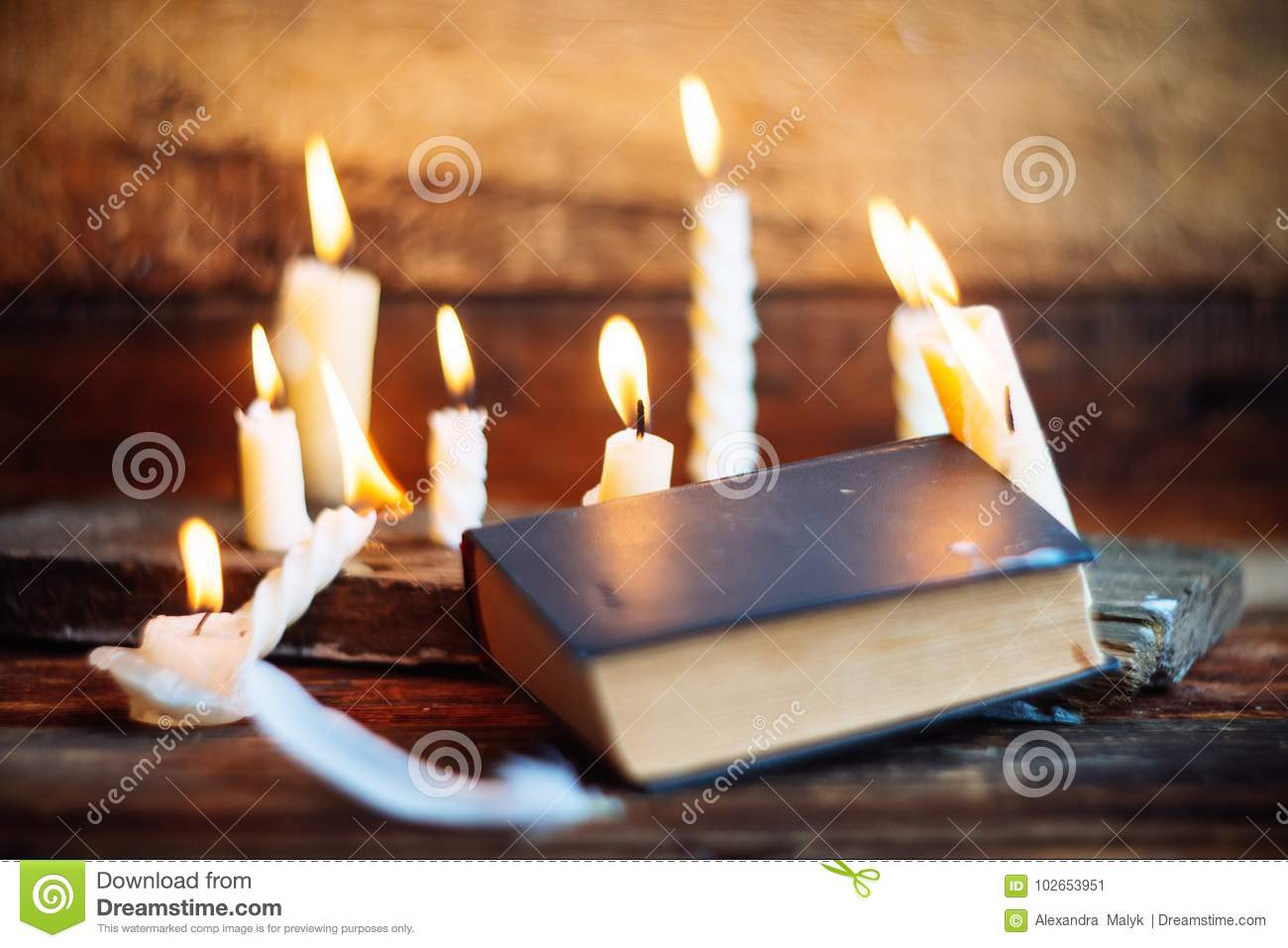 Three Magic Books In Candlelight On The Wooden Table In The