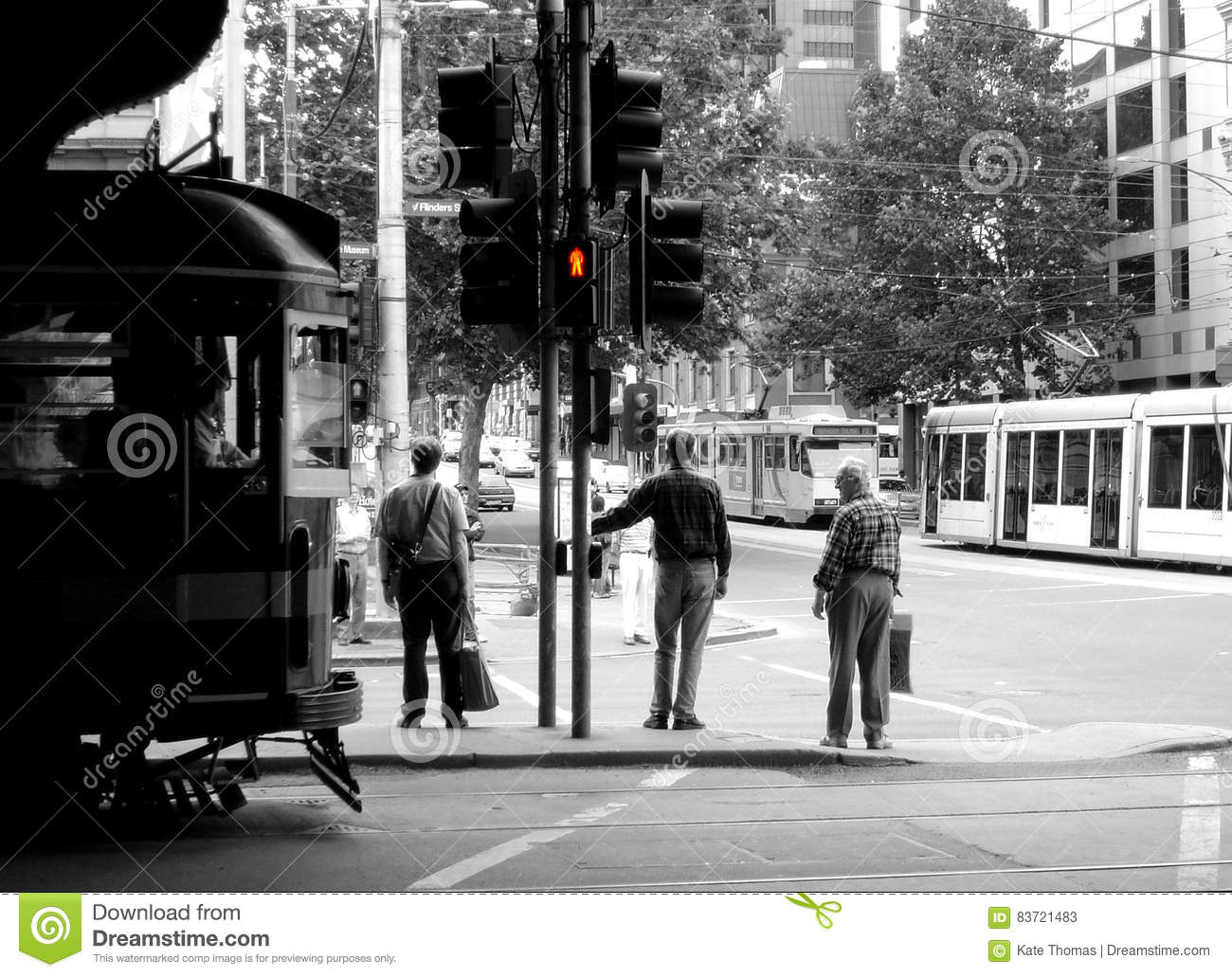 Three Men Wait To Cross Flinders Street In Melbourne, Australia Editorial Stock Photo