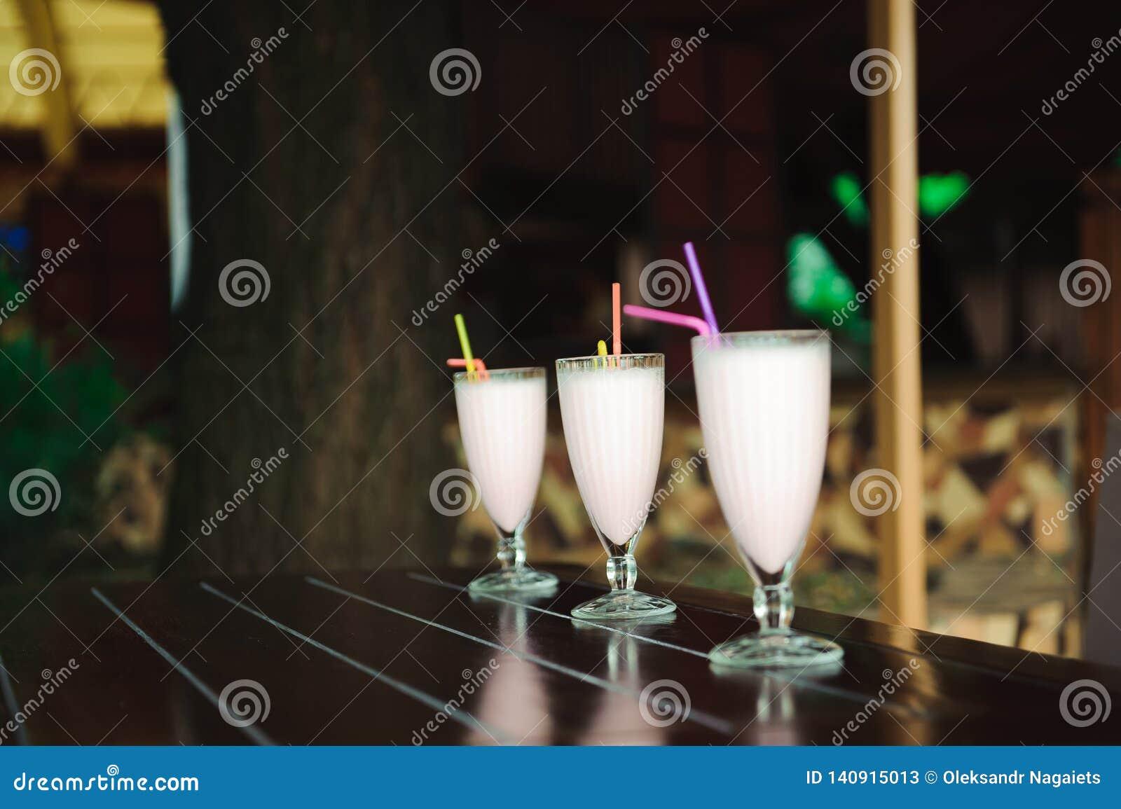 Three milkshakes and smoothies on wooden table.
