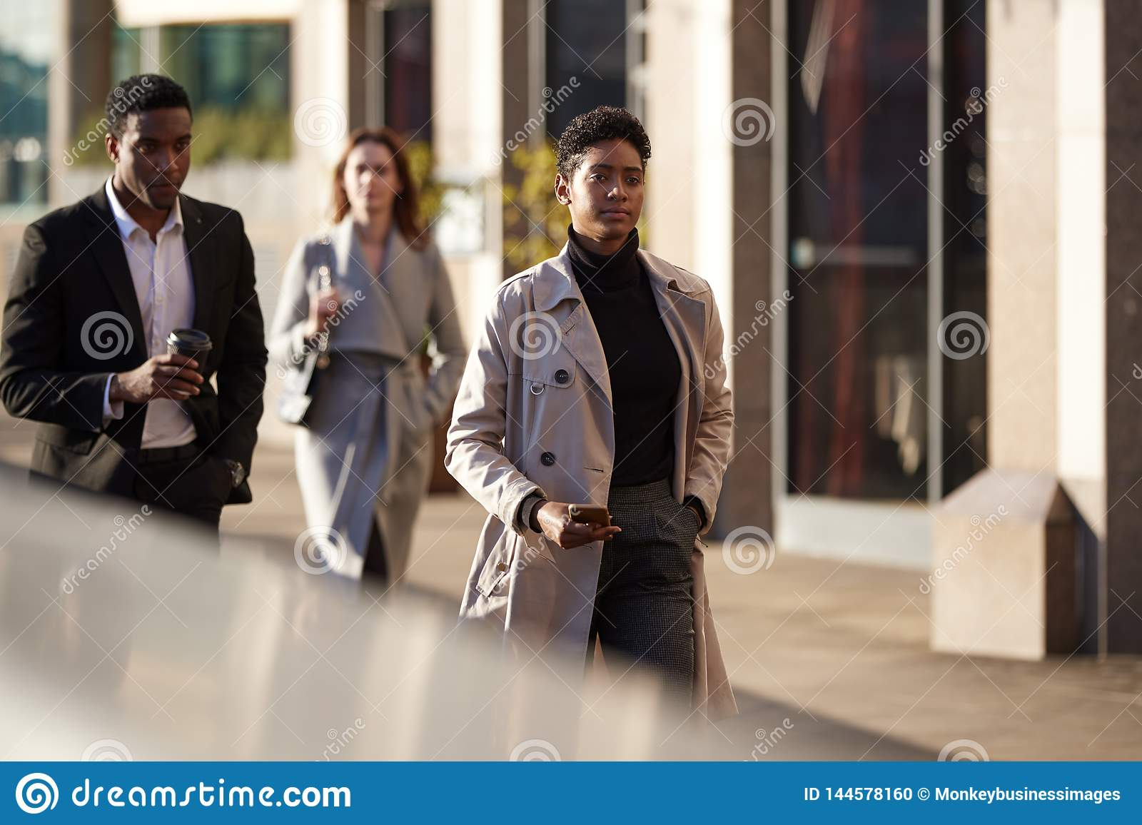 Three millennial city workers walking in a London street, selective focus