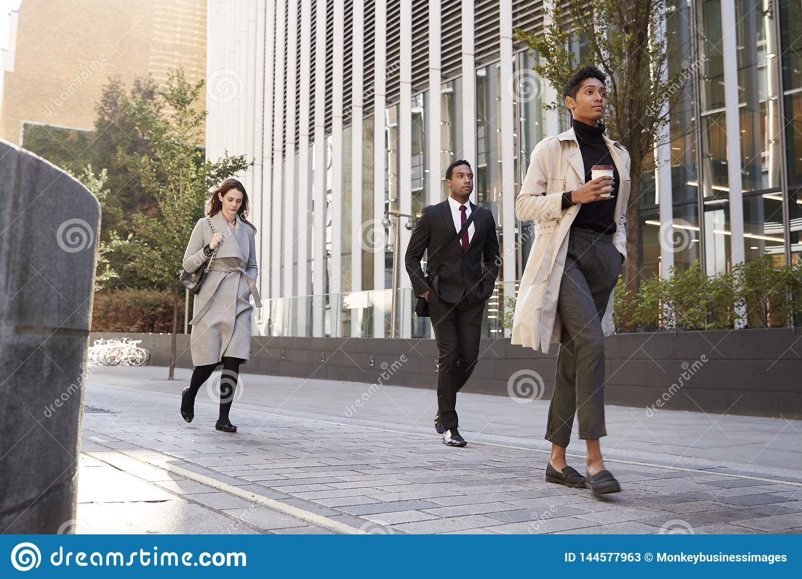 Three millennial city workers walking in the street, low angle, full length