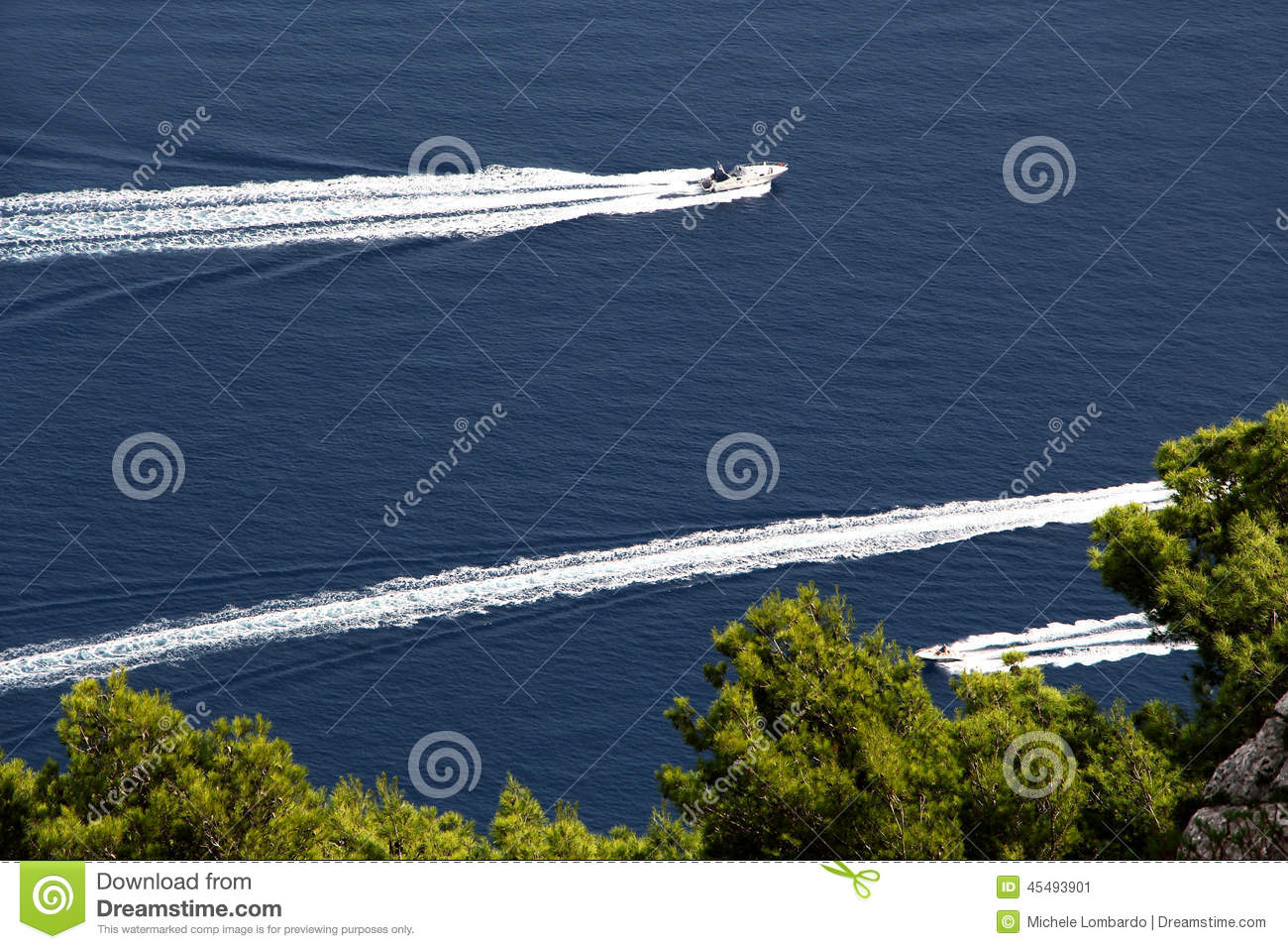 Three motorboats against a blue sea and trees