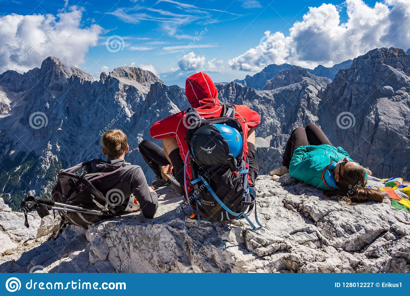 Three mountaineers sitting on the rock on the top of the Prisojnik mountain