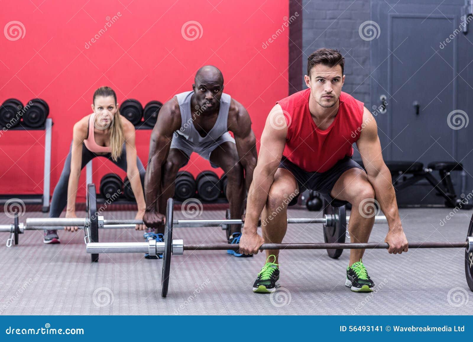 Three muscular athletes lifting barbells