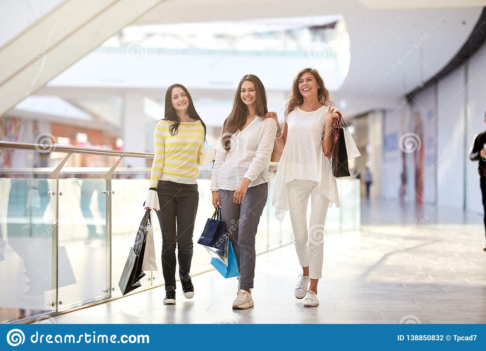 Three nice joyful girls dressed in nice casual clothes walk with lots of shopping bags in the mall. Shopping time
