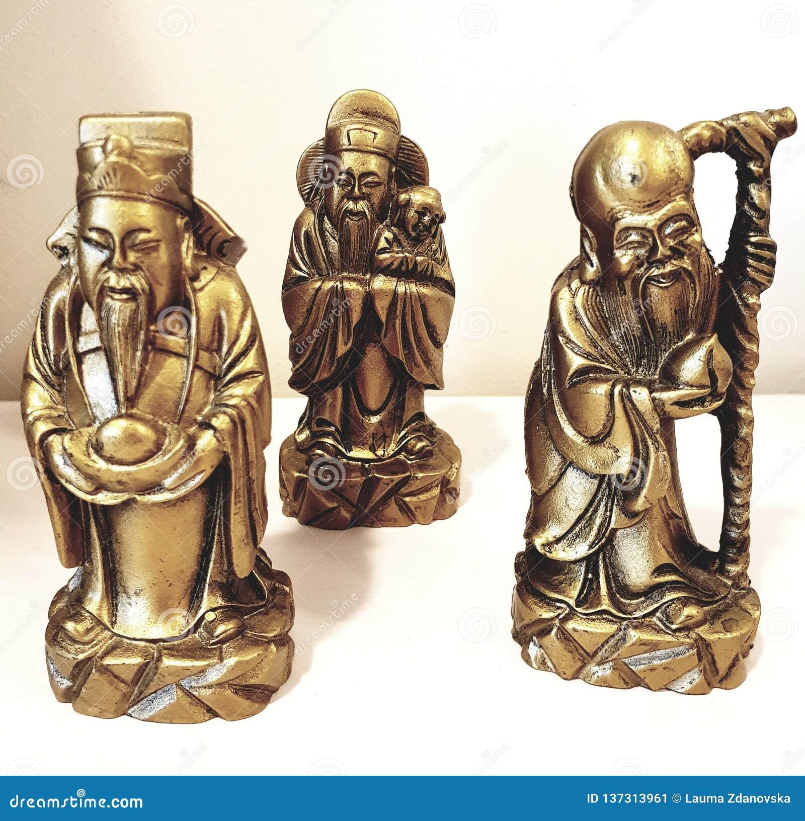 Three old asian guru figures